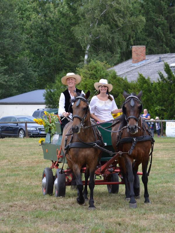 Jugendwartin Maren Ludwig auf dem Milchwagen mit Beifahrerin Katrin Stöver, vorne gehen Peggy und Paulina.